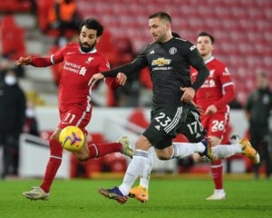 LIVERPOOL, ENGLAND - JANUARY 17: Luke Shaw of Manchester United  is put under pressure by Mohamed Salah of Liverpool during the Premier League match between Liverpool and Manchester United at Anfield on January 17, 2021 in Liverpool, England. Sporting stadiums around England remain under strict restrictions due to the Coronavirus Pandemic as Government social distancing laws prohibit fans inside venues resulting in games being played behind closed doors. (Photo by Paul Ellis - Pool/Getty Images)